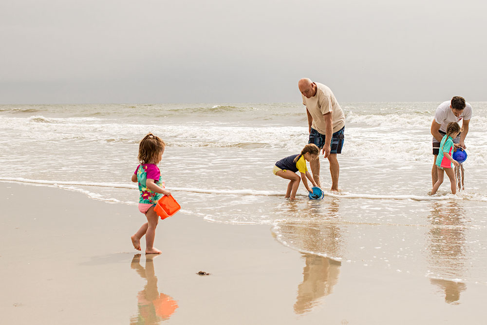 Nancy Elizabeth New Jersey Family Photographer | Grandpa filling up buckets in the ocean with kids | Beach Days Photography