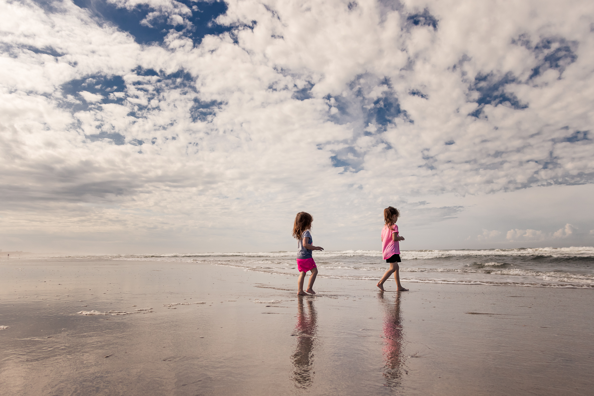 Nancy Elizabeth New Jersey Family Photographer | Clouds in Blue Sky Sisters Walking Toward Ocean | Beach Days Photography