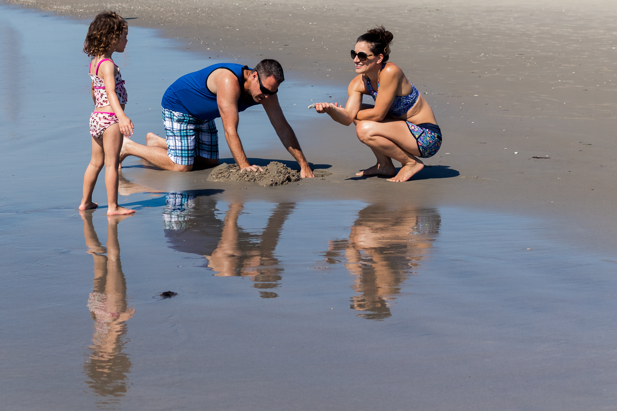 Nancy Elizabeth Photography | Jersey Shore Documentary Beach Photographer | Mom and Dad pLaying with Daughter in Sand with Reflection