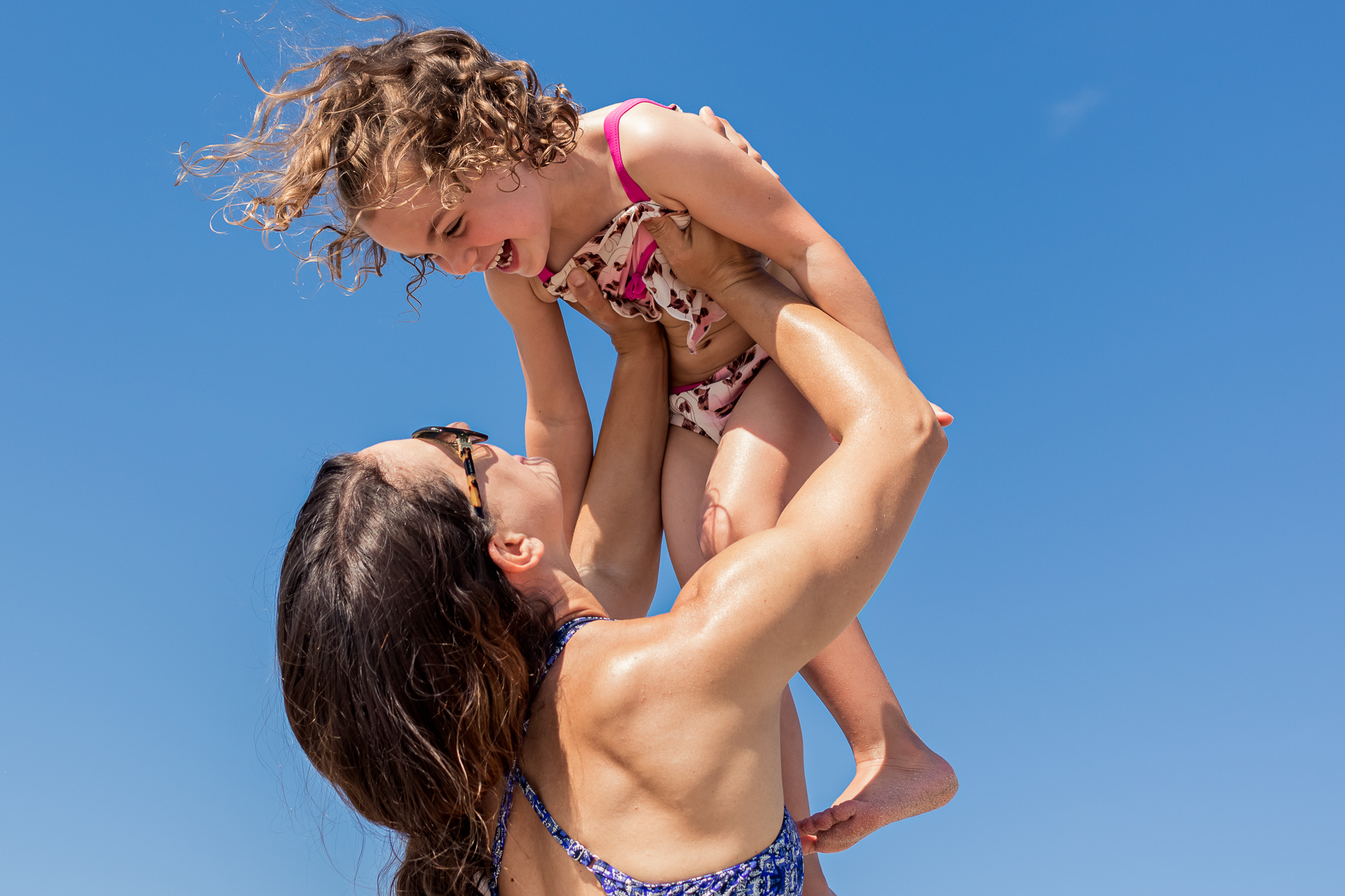 Nancy Elizabeth Photography | Jersey Shore Documentary Beach Photographer | Mom Lifting Daughter in Air Blue Sky