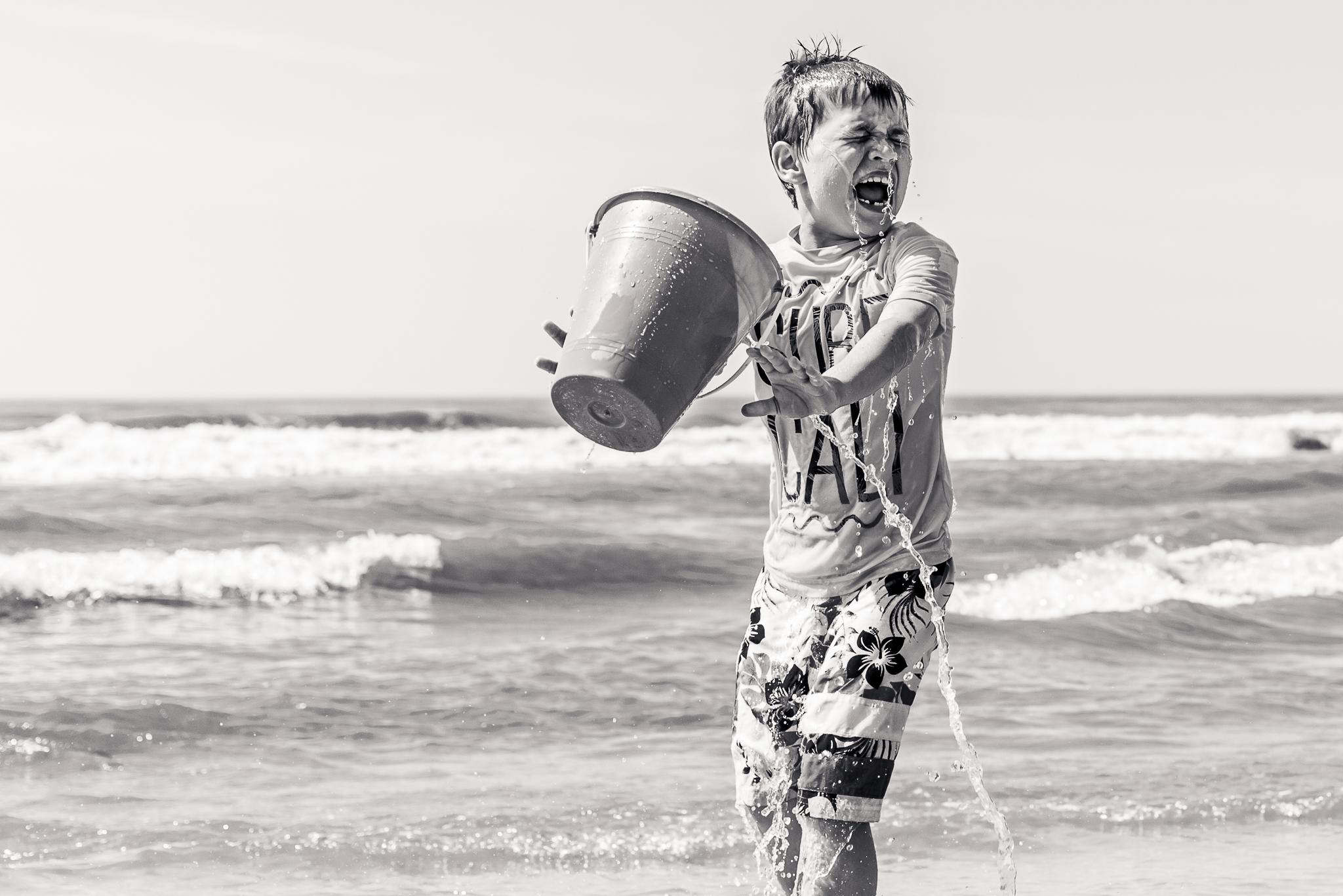 Nancy Elizabeth Documentary Beach Photographer,, Boy Throwing Bucket of Water