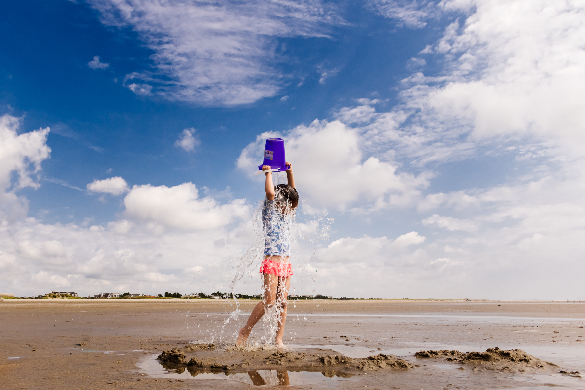New Jersey Beach Photographer, Documentary Beach Photography, Girl Dumping Water on Head Clouds in Blue Sky