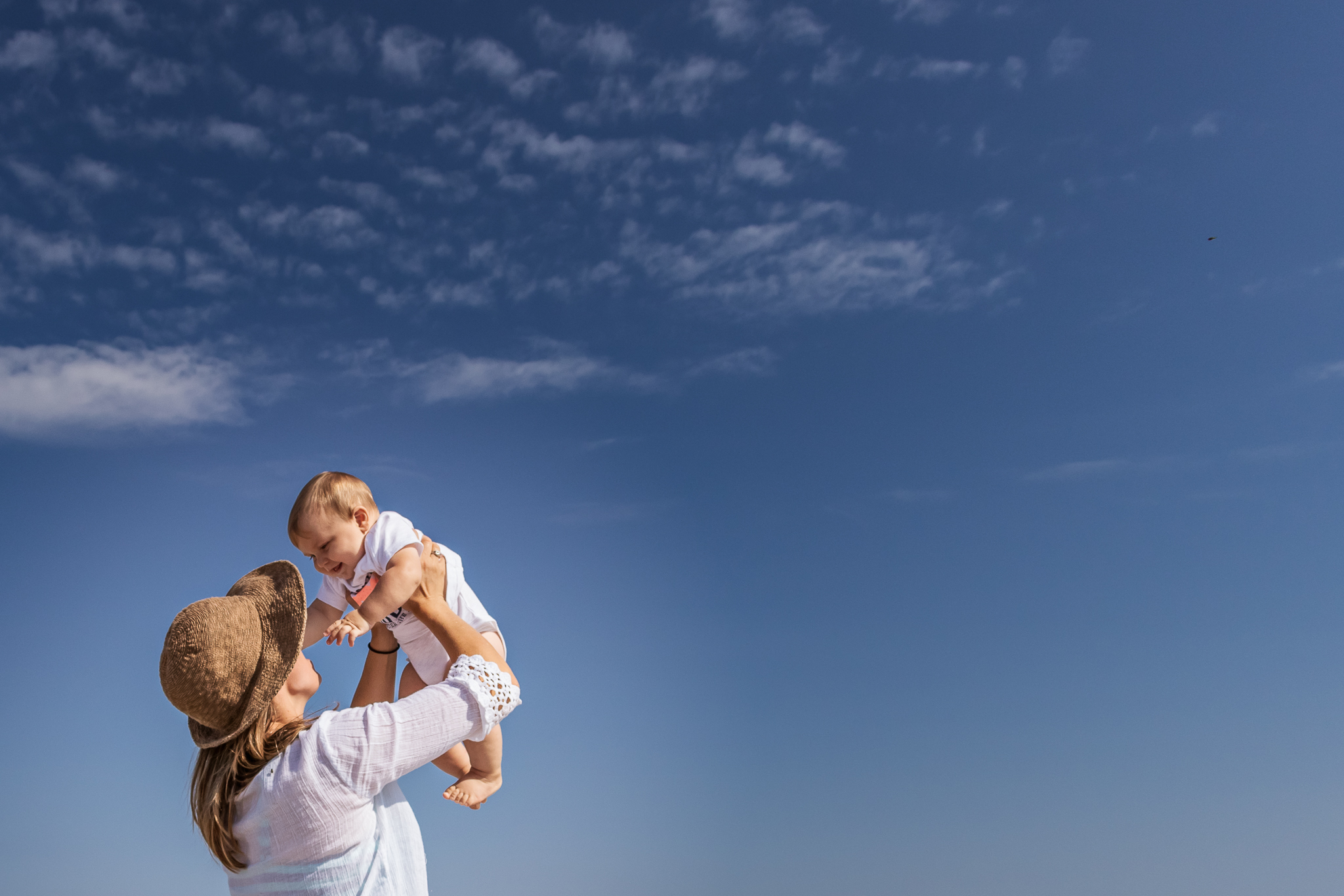 New Jersey Beach Photographer, Mom Lifting Son in Air with Blue Sky